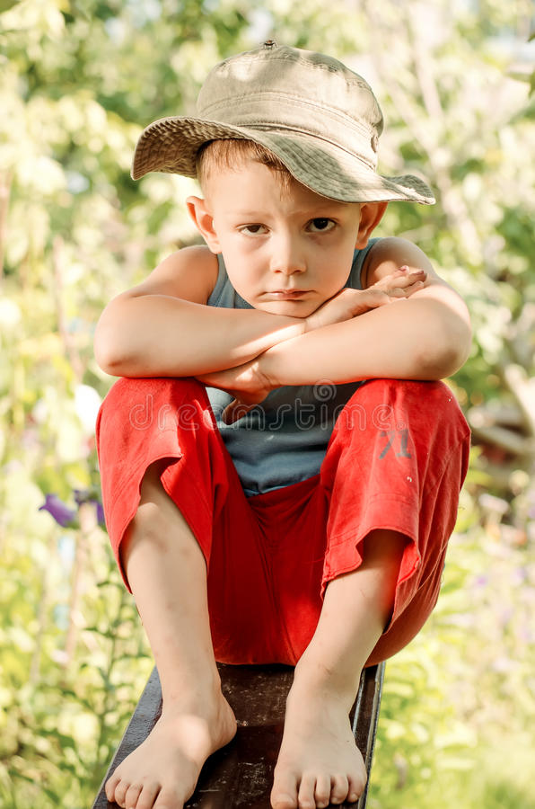 Στοχαστικό νέο αγόρι που κοιτάζει επίμονα στη κάμερα στοκ φωτογραφίες