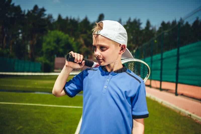 Στοχαστικό παιδί που κρατά τη ρακέτα αντισφαίρισης στοκ εικόνα