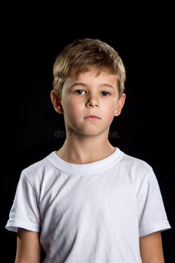 Στοχαστικό πορτρέτο παιδιών, ευφυές αγόρι στο μαύρο υπόβαθρο που φαίνεται ευθύ στοκ φωτογραφίες