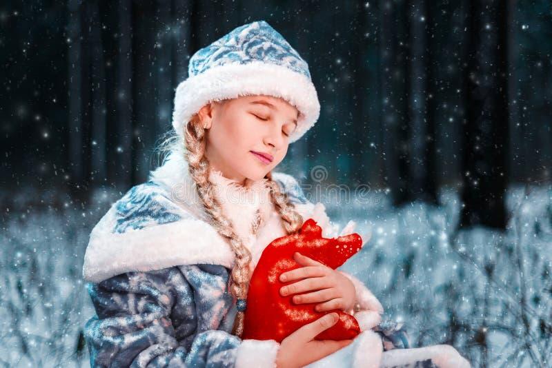 Στοχαστικό, ρομαντικό κορίτσι χιονιού το μικρό κορίτσι σε ένα μυθικό χειμερινό δάσος κρατά στα χέρια της μια τσάντα με τα δώρα Δι στοκ φωτογραφία