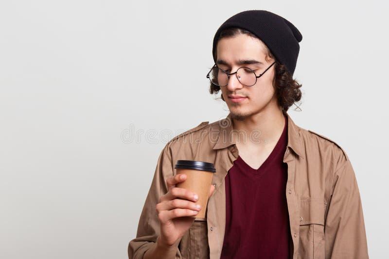 Στοχαστικό σκεπτικό yougster που έχει papercup του καφέ, κρατώντας το ζεστό ποτό σε ένα χέρι, εξετάζοντας προσεκτικά το, τοποθέτη στοκ φωτογραφίες με δικαίωμα ελεύθερης χρήσης