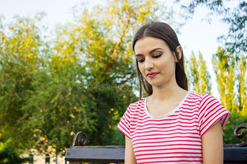 Στοχαστικό όμορφο κορίτσι που κάθεται μόνο υπαίθρια στο πάρκο στοκ εικόνα