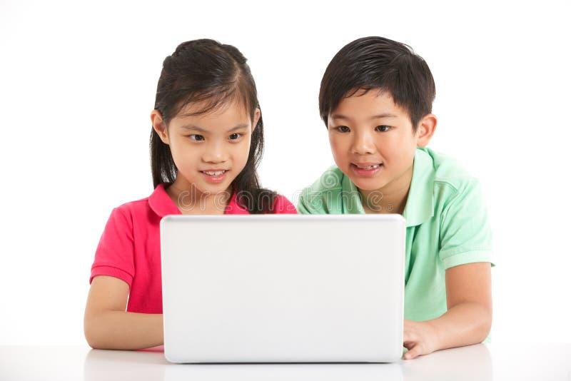 Στούντιο που καλύπτονται δύο κινεζικών παιδιών με το lap-top στοκ εικόνα