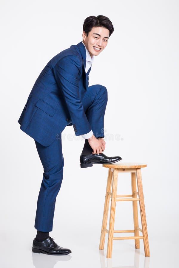 Στούντιο που πυροβολείται ενός νέου ασιατικού επιχειρηματία που φορά ένα κορδόνι που αυξάνει το πόδι του σε μια καρέκλα στοκ εικόνες