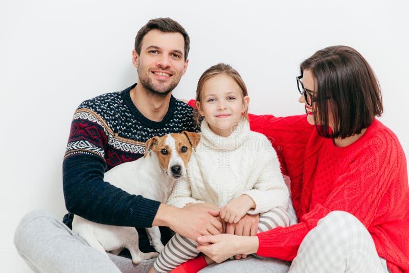 Στούντιο που πυροβολείται της ευτυχούς οικογένειας τριών οικογενειακών μελών και σκυλιού, emb στοκ εικόνες με δικαίωμα ελεύθερης χρήσης