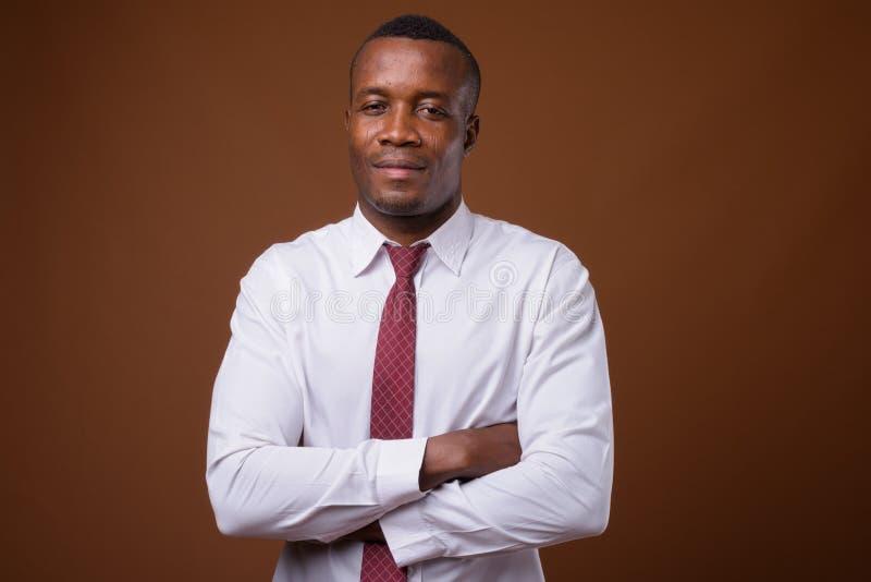 Στούντιο που πυροβολείται του νέου αφρικανικού επιχειρηματία ενάντια στο καφετί backgroun στοκ φωτογραφία με δικαίωμα ελεύθερης χρήσης