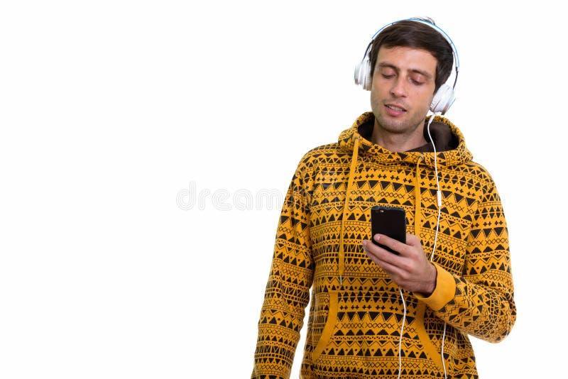 Στούντιο που πυροβολείται του νέου όμορφου ατόμου που ακούει τη μουσική χρησιμοποιώντας στοκ εικόνες