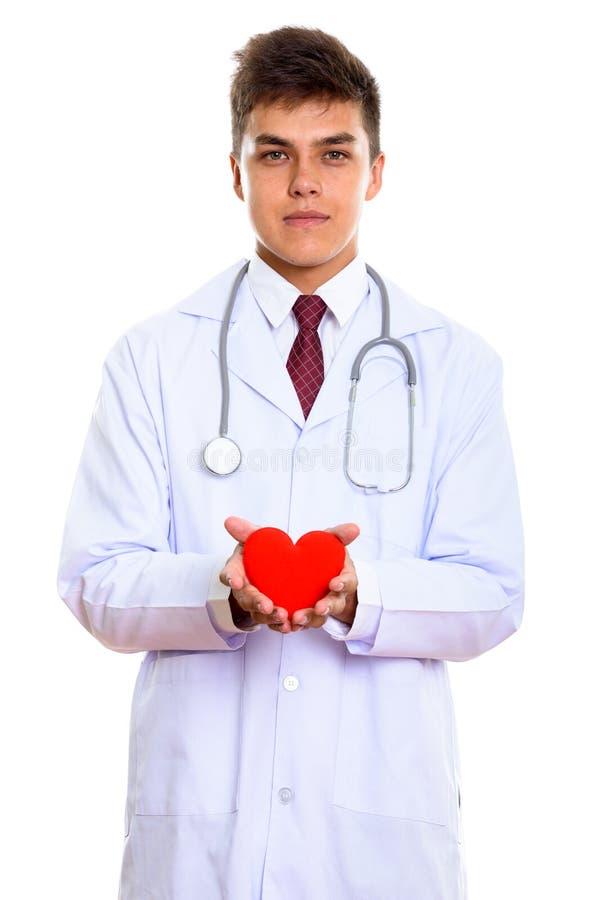 Στούντιο που πυροβολείται του νέου όμορφου γιατρού ατόμων που κρατά την κόκκινη καρδιά με στοκ φωτογραφία με δικαίωμα ελεύθερης χρήσης