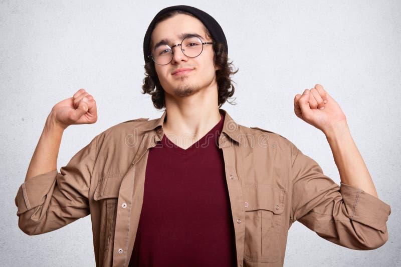 Στούντιο που πυροβολείται του νεαρού άνδρα στην ΚΑΠ, maroom μπλούζα, καφετιά σακάκι και θεάματα που παρουσιάζουν μυς Απομονωμένος στοκ εικόνα με δικαίωμα ελεύθερης χρήσης