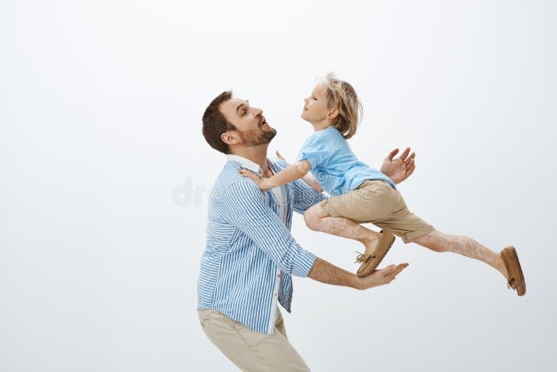Στούντιο που πυροβολείται του πατέρα που πιάνει το χαριτωμένο ξανθό γιο που πηδά από τον πίνακα, που παίζει και που γύρω, που φρο στοκ εικόνες