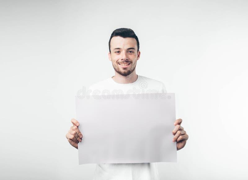 στο άσπρο υπόβαθρο το άτομο κρατά μια αφίσα γενειοφόρο στοκ φωτογραφία με δικαίωμα ελεύθερης χρήσης