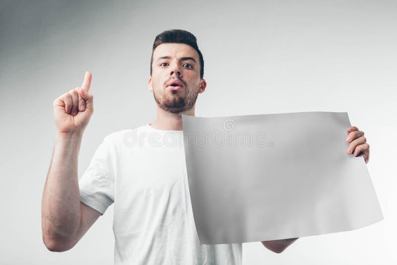 στο άσπρο υπόβαθρο το άτομο κρατά μια αφίσα γενειοφόρο στοκ φωτογραφίες