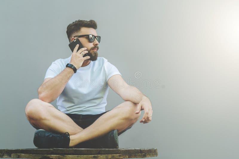 Στο αριστερό μέρος της εικόνας το νέο ελκυστικό γενειοφόρο άτομο hipster στα γυαλιά ηλίου και την άσπρη μπλούζα κάθεται cross-leg στοκ φωτογραφία