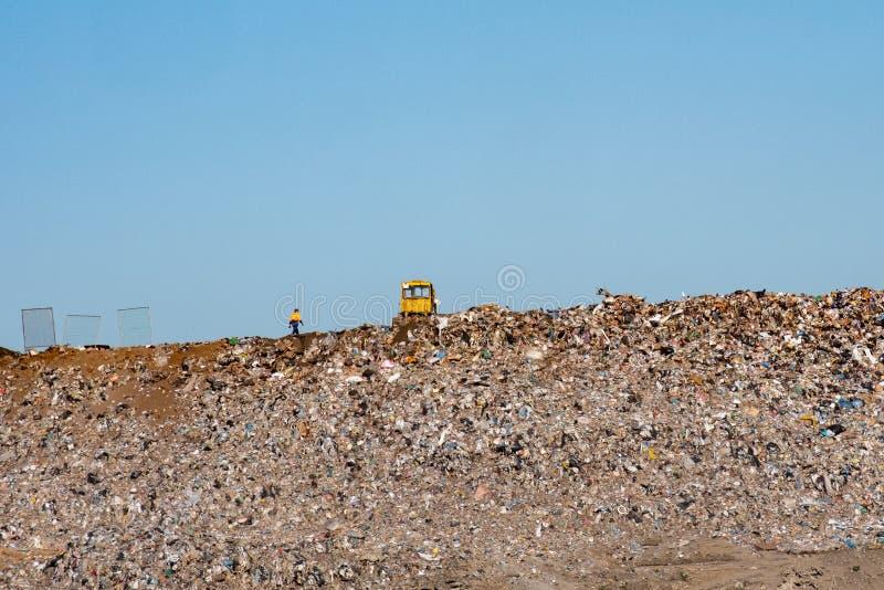 Στο βουνό των απορριμάτων στην απόρριψη ένα μεγάλο κίτρινο τρακτέρ, πολύς ουρανός στοκ φωτογραφίες με δικαίωμα ελεύθερης χρήσης