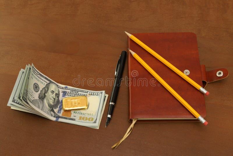 Στο γραφείο γραφείων είναι δολάρια μετρητών, χρυσοί φραγμοί Σημειωματάριο για τις σημειώσεις και τη μάνδρα στοκ εικόνα με δικαίωμα ελεύθερης χρήσης