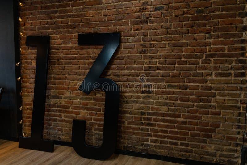 Στο δωμάτιο κοντά στον εκλεκτής ποιότητας τουβλότοιχο υπάρχουν μεγάλοι μαύροι αριθμοί 13 Αρχικό εσωτερικό του στούντιο αναδρομικό στοκ εικόνες με δικαίωμα ελεύθερης χρήσης