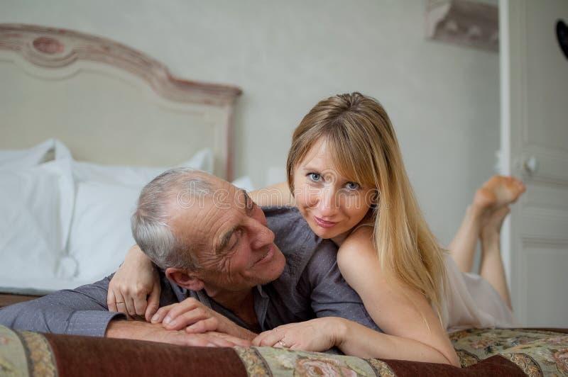 Στο εσωτερικό πορτρέτο του χαρούμενου ζεύγους με τη διαφορά ηλικίας που βρίσκεται στο κρεβάτι στοκ εικόνα