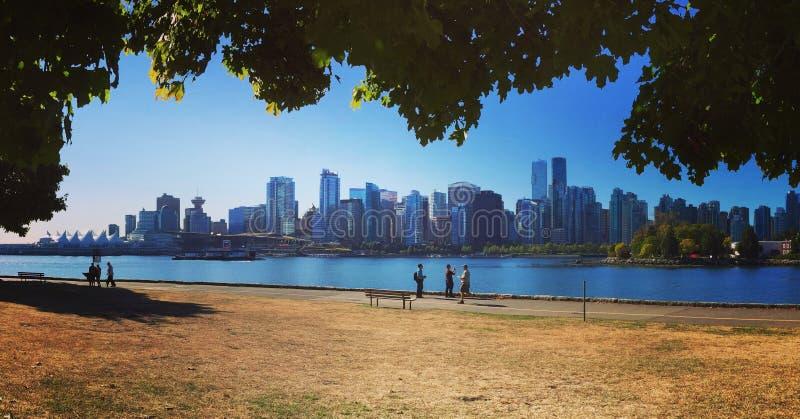 Στο κέντρο της πόλης ορίζοντας του Βανκούβερ που αντιμετωπίζεται από το ίχνος seawall στο πάρκο του Stanley στοκ εικόνες