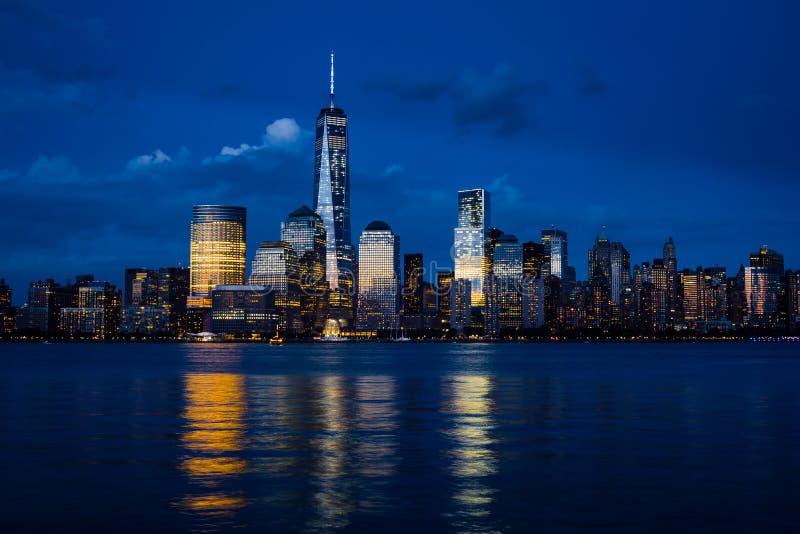 Στο κέντρο της πόλης ορίζοντας του Μανχάταν πόλεων της Νέας Υόρκης με τους ουρανοξύστες που φωτίζονται πέρα από το πανόραμα ποταμ στοκ φωτογραφία