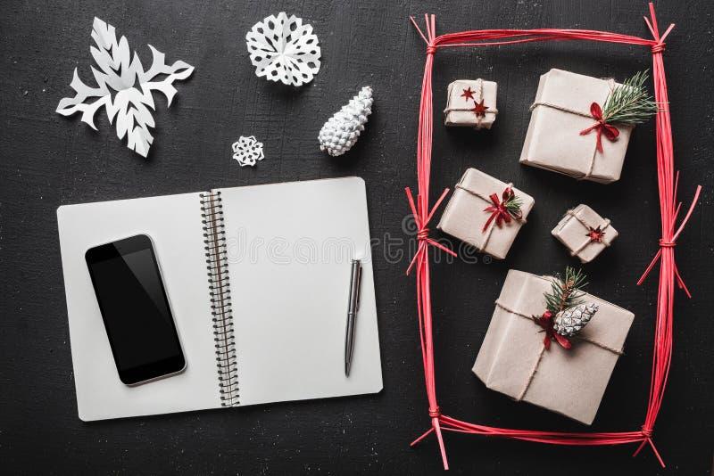Στο μαύρο υπόβαθρο, πολλά δώρα και χειροποίητα στοιχεία, ένα βιβλιάριο όπου μπορείτε να αντιγράψετε ένα μήνυμα χαιρετισμού από το στοκ φωτογραφία