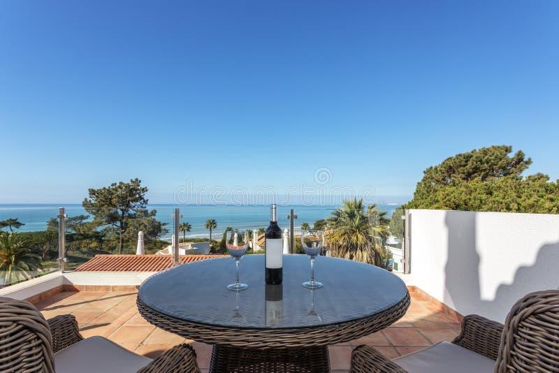 Στο πεζούλι ένα μπουκάλι του κρασιού και των γυαλιών με μια άποψη της θάλασσας στοκ φωτογραφίες