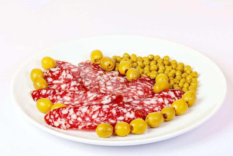 Στο πιάτο βρίσκεται τεμαχισμένο λουκάνικο, πράσινα μπιζέλια, και ελιές στοκ φωτογραφία