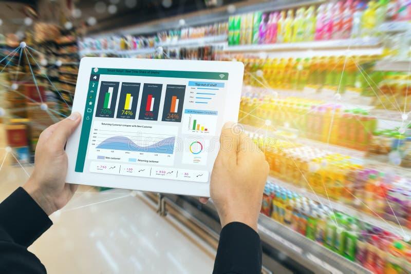 Στο πλαίσιο της έξυπνης λιανικής πώλησης με την έννοια του μέλλοντος, ο λιανοπωλητής κρατά το tablet και χρησιμοποιεί δεδομένα επ στοκ φωτογραφίες