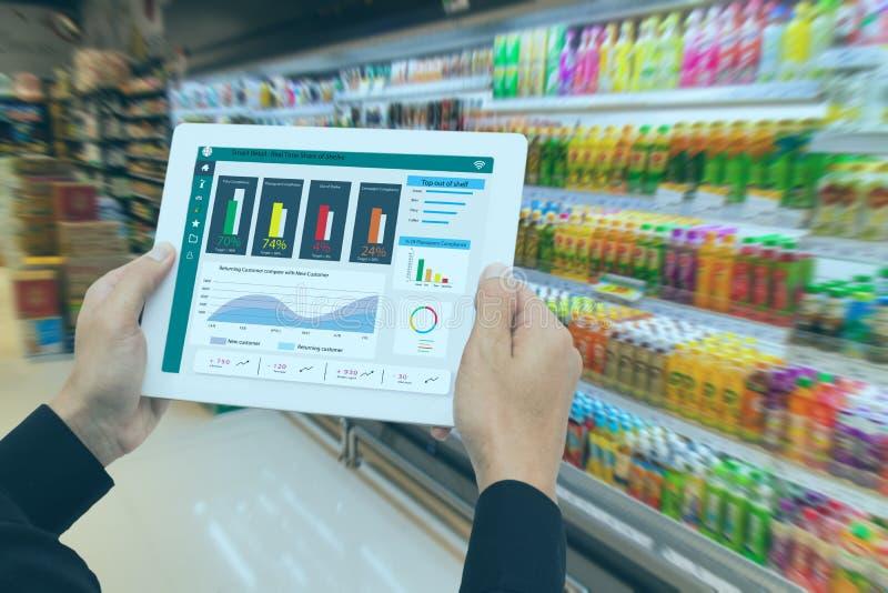 Στο πλαίσιο της έξυπνης λιανικής πώλησης με την έννοια του μέλλοντος, ο λιανοπωλητής κρατά το tablet και χρησιμοποιεί δεδομένα επ στοκ φωτογραφίες με δικαίωμα ελεύθερης χρήσης