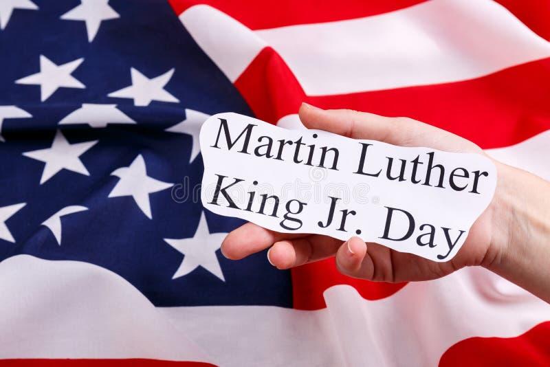 Στο υπόβαθρο της αμερικανικής σημαίας, το χέρι του ατόμου κρατά την επιγραφή Martin Luther King Jr ημέρα στοκ φωτογραφίες με δικαίωμα ελεύθερης χρήσης