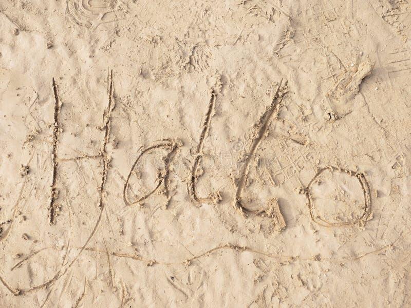 Στρέθιμο της προσοχής παιδιών του hallo λέξης στην άμμο στην παραλία του κόλπου Επιστολές που γράφονται στην άμμο στοκ φωτογραφίες