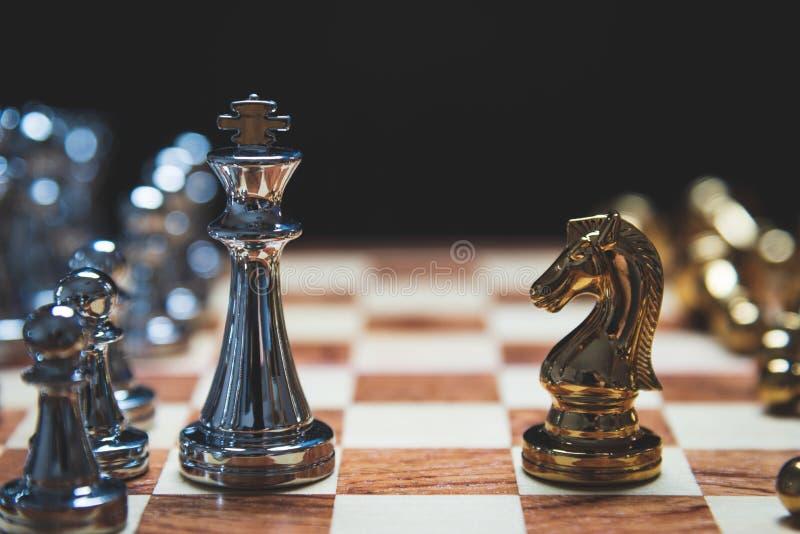 Στρατηγική της ισχυρής ηγεσίας ως βασιλιάς και της αδύνατης ηγεσίας ως άλογο που αντιμετωπίζουν η μια την άλλη στον ξύλινο πίνακα στοκ φωτογραφίες