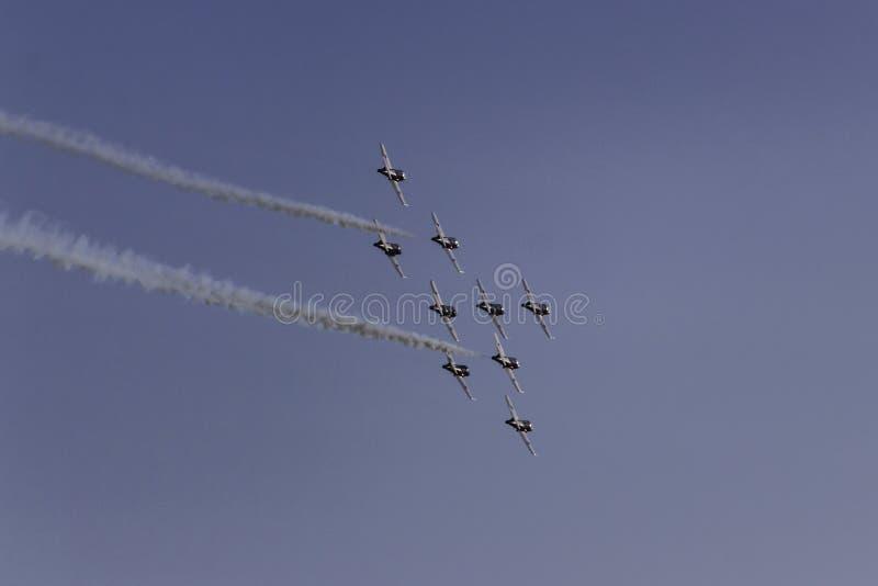 Στρατιωτικά αεριωθούμενα αεροπλάνα που πετούν μακριά στο σχηματισμό με τα άσπρα ίχνη καπνού στοκ φωτογραφίες με δικαίωμα ελεύθερης χρήσης