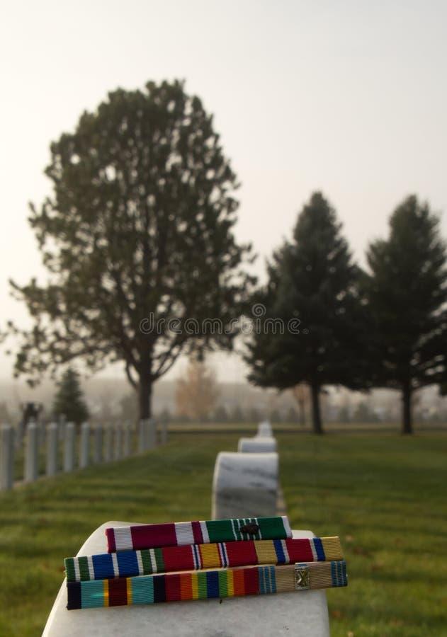 Στρατιωτικές κορδέλλες βραβείων σε Veteran& x27 ταφόπετρα του s στοκ εικόνα με δικαίωμα ελεύθερης χρήσης