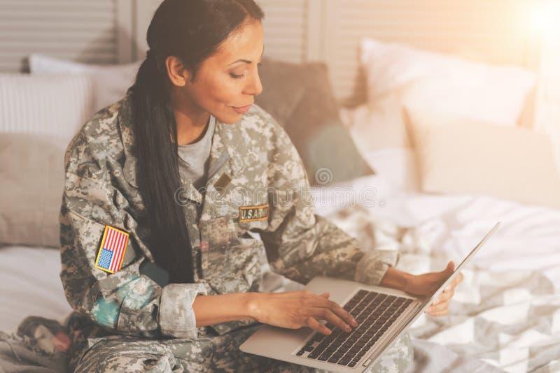 Στρατιωτική γυναίκα που κουβεντιάζει στο lap-top στο κρεβάτι στοκ φωτογραφία