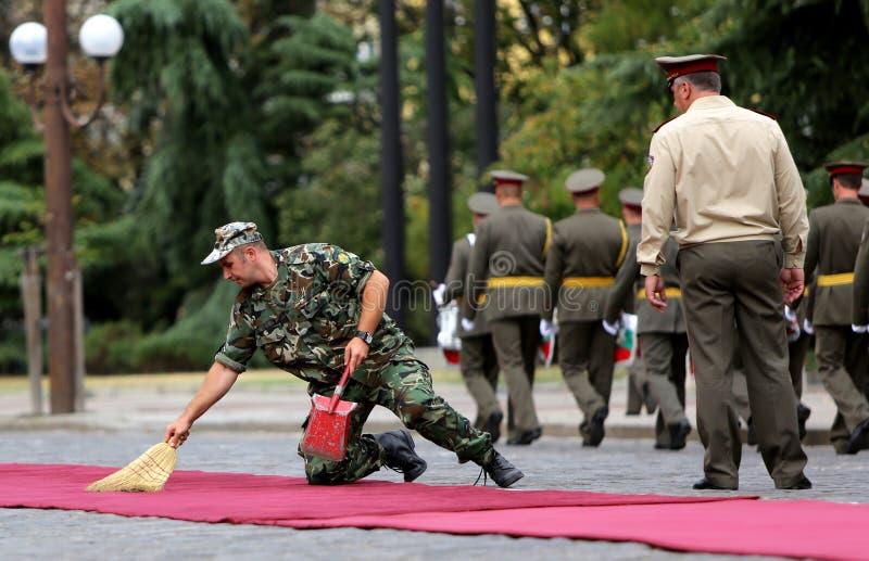 Στρατιωτικός καθαρίζοντας ένα κόκκινο χαλί στοκ φωτογραφία