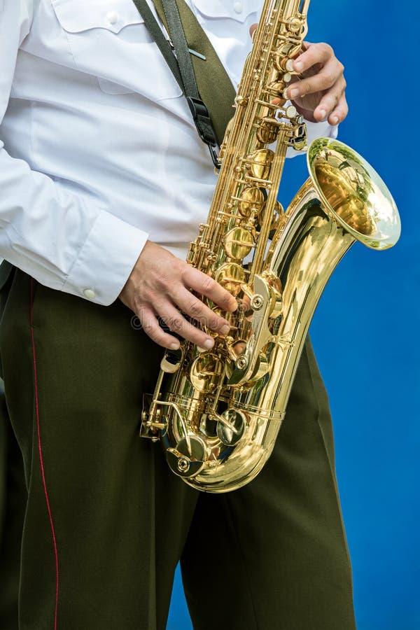 Στρατιωτικός μουσικός ορχηστρών πνευστ0ών από χαλκό με το saxophone στα χέρια του στοκ φωτογραφία