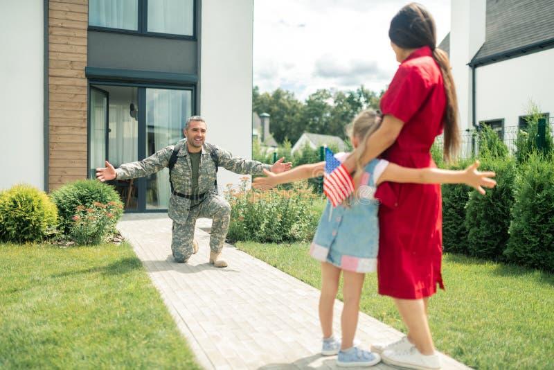 Στρατιωτικός που στέκεται στο γόνατό του βλέποντας τη σύζυγο και την κόρη στοκ φωτογραφίες