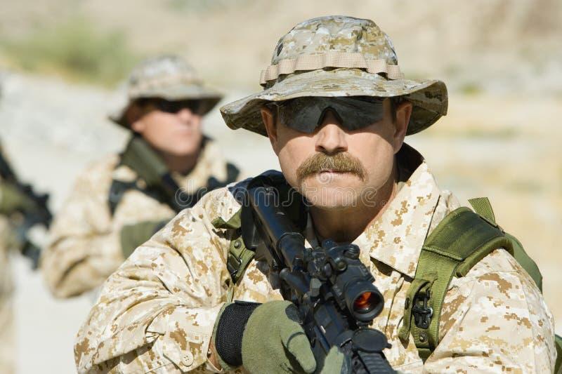 Στρατιώτες με τα τουφέκια ελεύθερων σκοπευτών στην αποστολή στοκ εικόνες