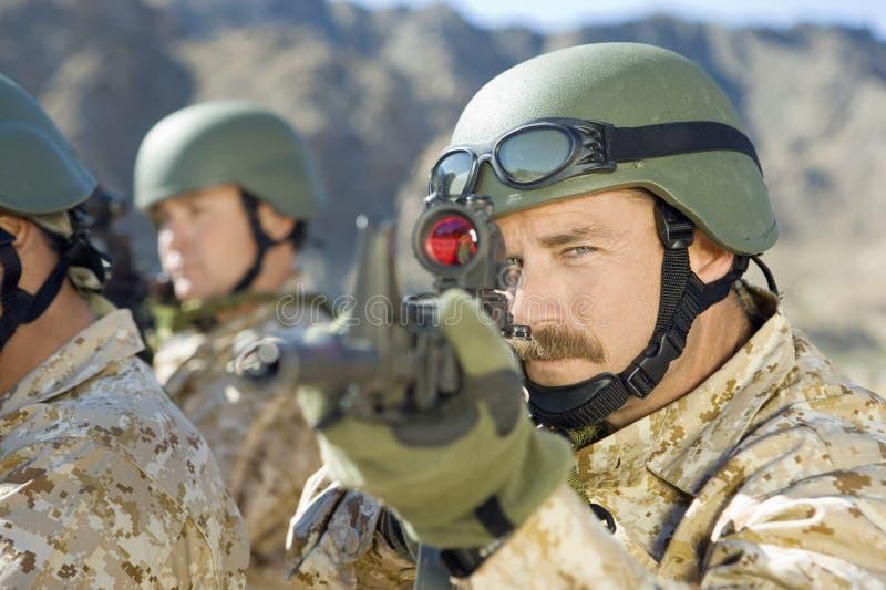 Στρατιώτες που στοχεύουν τα τουφέκια στοκ εικόνες