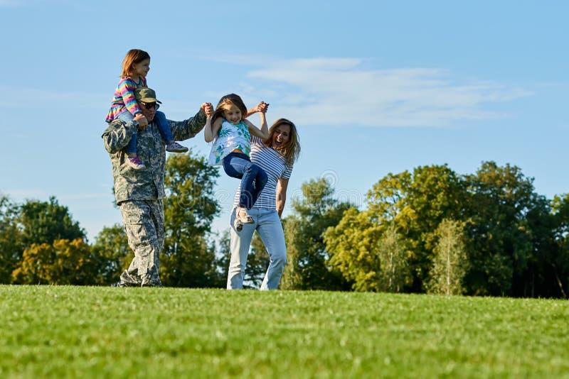 Στρατιώτης και η οικογένειά του που έχουν τη διασκέδαση υπαίθρια στοκ εικόνα