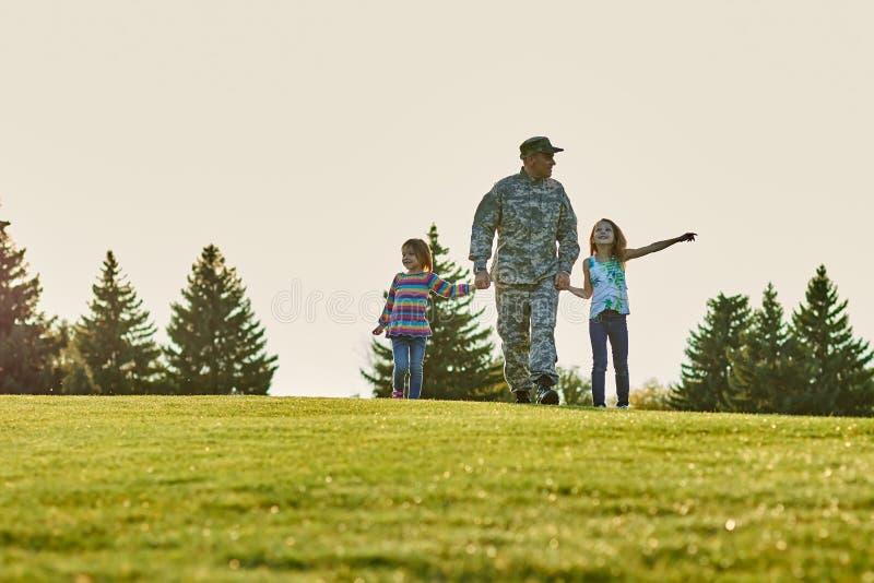 Στρατιώτης και οι κόρες του στη χλόη στοκ φωτογραφία με δικαίωμα ελεύθερης χρήσης