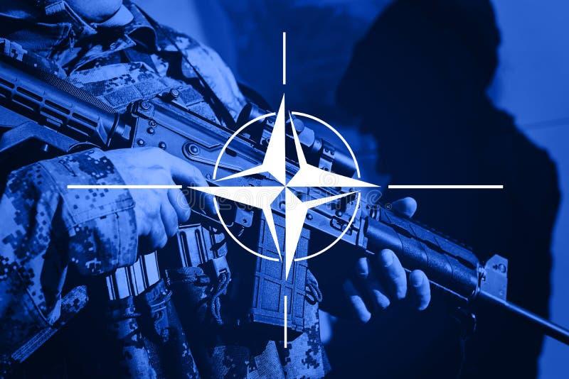 Στρατιώτης με το πολυβόλο με τη σημαία της συμμαχίας του ΝΑΤΟ στοκ εικόνες