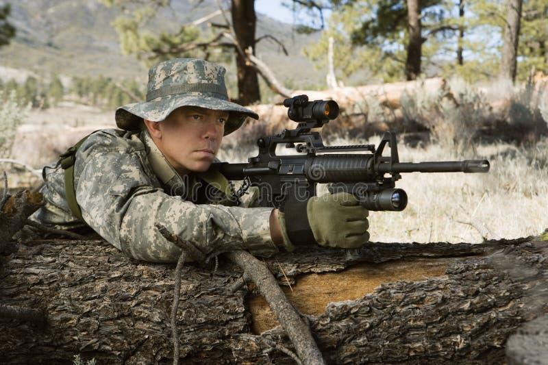 Στρατιώτης με το πολυβόλο που κλίνει στο κούτσουρο στοκ εικόνες