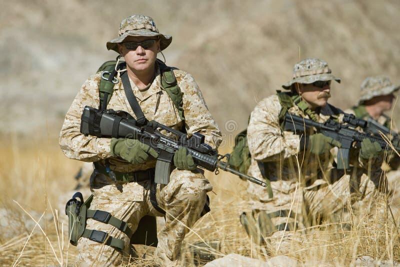 Στρατιώτης με το τουφέκι επιτηρώντας ομάδας κατά τη διάρκεια του πολέμου στοκ φωτογραφία