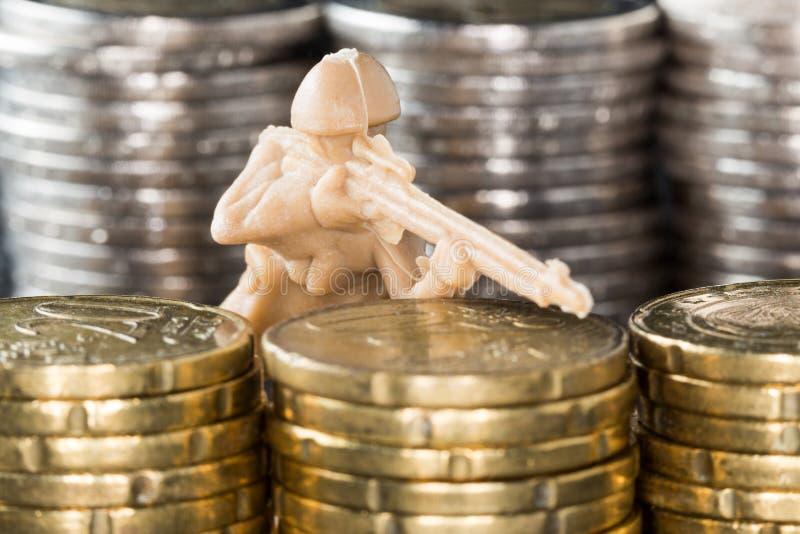 Στρατιώτης παιχνιδιών μέσα - μεταξύ των σωρών των νομισμάτων στοκ φωτογραφία με δικαίωμα ελεύθερης χρήσης