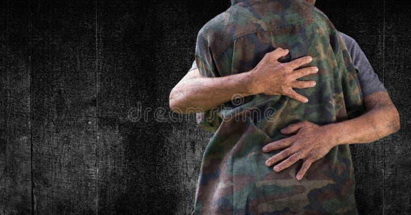 Στρατιώτης που αγκαλιάζει το μέσο τμήμα ενάντια στη μαύρες ξύλινες επιτροπή και grunge την επικάλυψη στοκ εικόνα