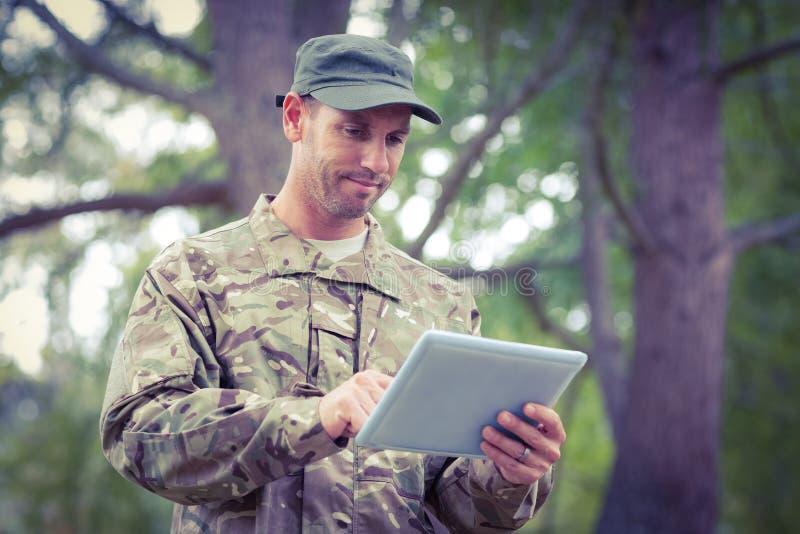 Στρατιώτης που εξετάζει το PC ταμπλετών στο πάρκο στοκ εικόνες