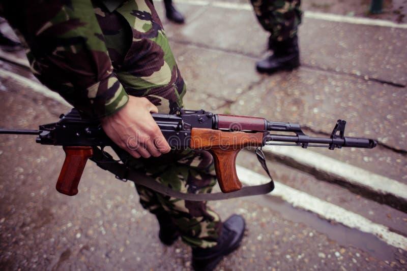 Στρατιώτης που κρατά ένα αυτόματο τουφέκι στοκ εικόνα με δικαίωμα ελεύθερης χρήσης