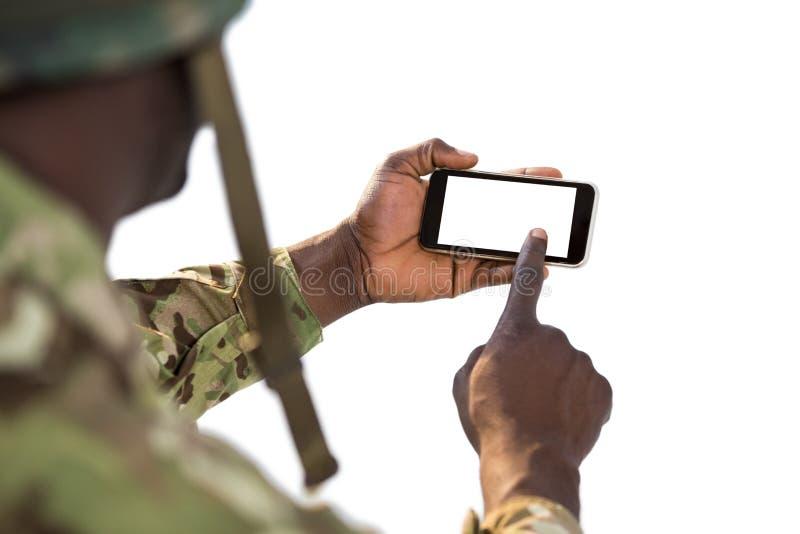 Στρατιώτης που χρησιμοποιεί ένα κινητό τηλέφωνο στοκ εικόνα