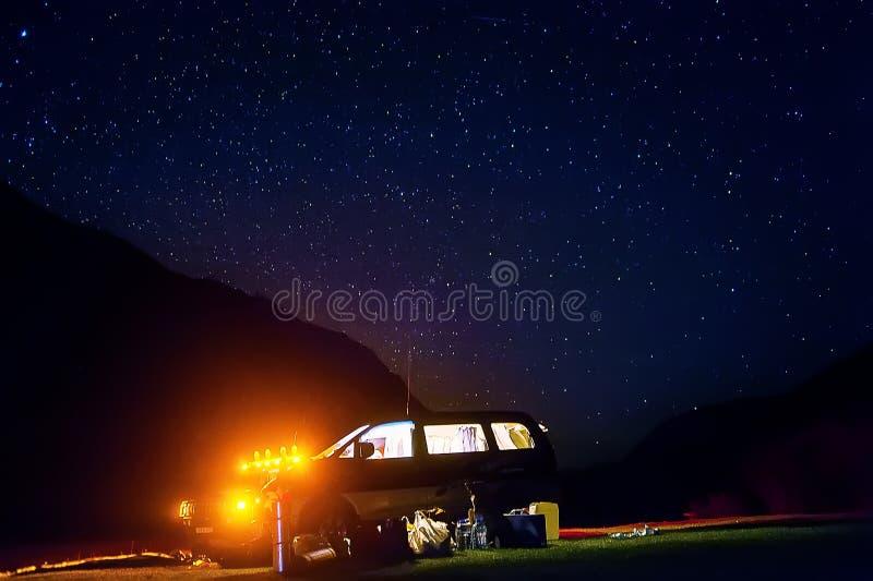 Στρατοπέδευση με τις σκηνές και αυτοκίνητο κάτω από τα αστέρια Υπόλοιπο σε μια πυρά προσκόπων κάτω από το καταπληκτικό σύνολο νυχ στοκ εικόνες
